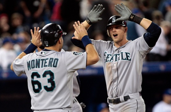 Michael Saunders celebrates with Jesus Montero after his 10th inning grand slam during Friday's 9-5 win in Toronto. (Getty Images)