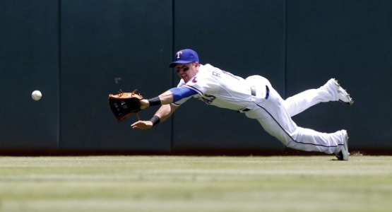 Texas Rangers center fielder Dan Robertson (19) dives for a ball hit by Los Angeles Angels Josh Hamilton (32) for a single in the first inning of a Major League Baseball Game at Globe Life Park, Sunday, July 13, 2014, in Arlington, Texas. (Richard W. Rodriguez/Fort Worth Star-Telegram/MCT via Getty Images)
